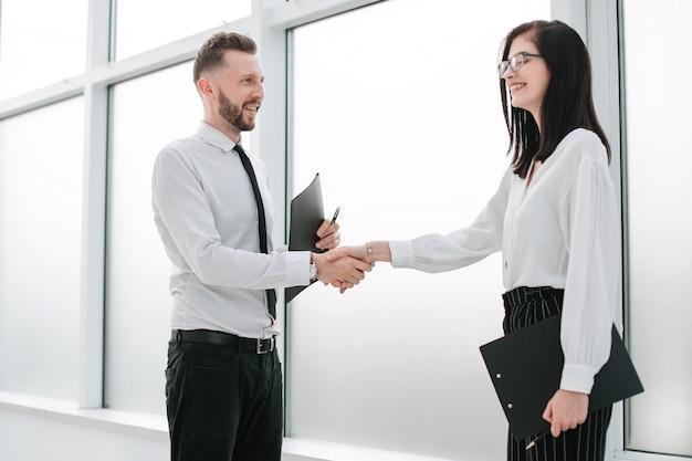 ビジネスセンターのロビーでの従業員の握手。協力の概念