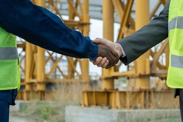 Рукопожатие инженеров африканских и кавказских национальностей против строительной площадки