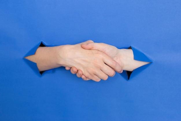 Рукопожатие женских рук на синем фоне. женские вставлены в бумажный фон. место для надписи.