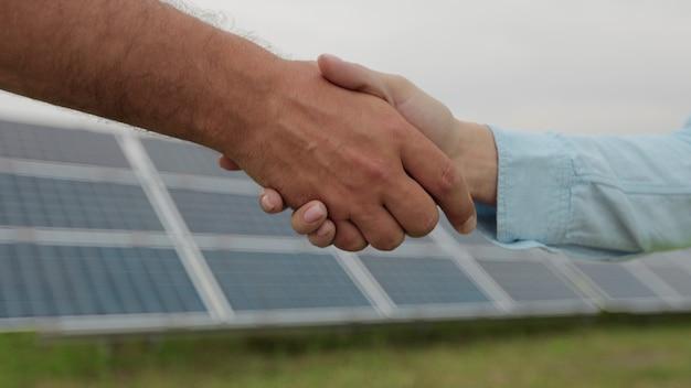 Рукопожатие мужчины и женщины на фоне солнечных батарей. концепция зеленой энергии. поле солнечных батарей.