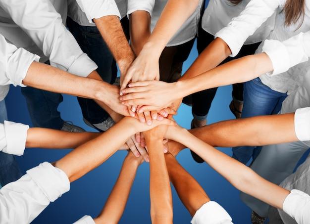 多くの若いビジネスマンの握手、チームワークの概念