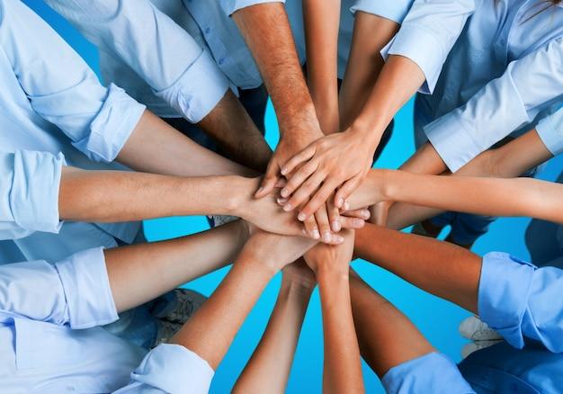 Рукопожатие многих молодых деловых людей, концепция совместной работы