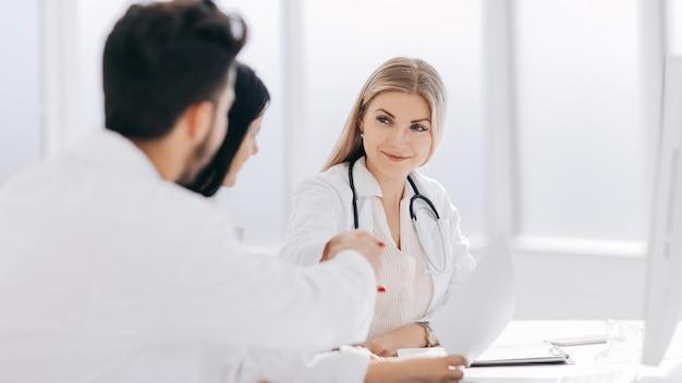 オフィスのデスクでの医療関係者の握手。健康の概念