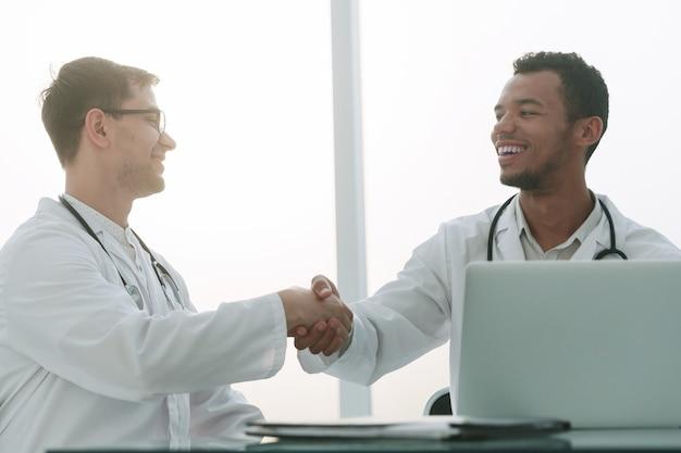 Рукопожатие коллег-врачей, сидящих за столом. концепция здоровья