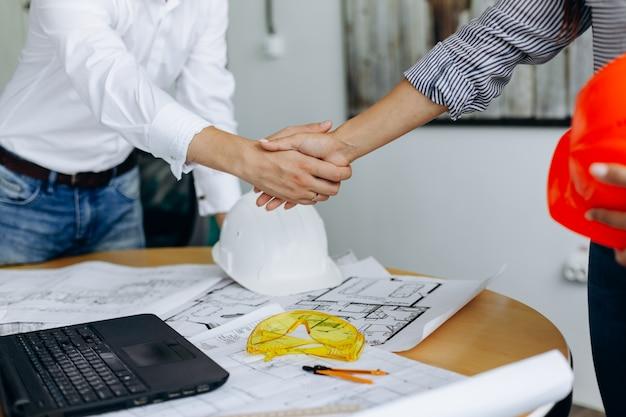 建築家の作業と計画の青写真後の2つのビジネスマンの握手