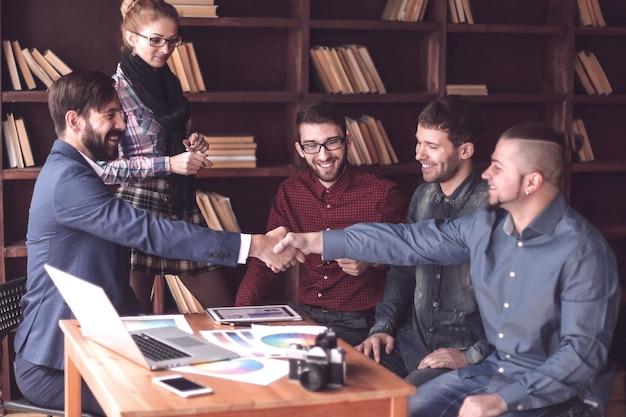Рукопожатие двух дизайнеров на рабочей встрече в офисе. фото с копией пространства
