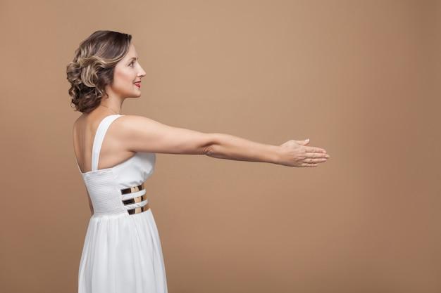 Рукопожатие, сторона профиля. концепция эмоций и чувств. студийный снимок, закрытый, изолированный на светло-коричневом фоне