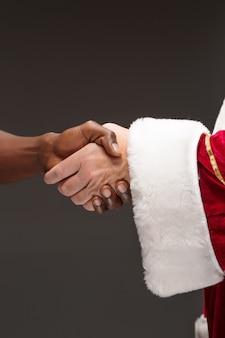 La stretta di mano della mano di babbo natale e la mano dell'uomo africano. buon natale concetto