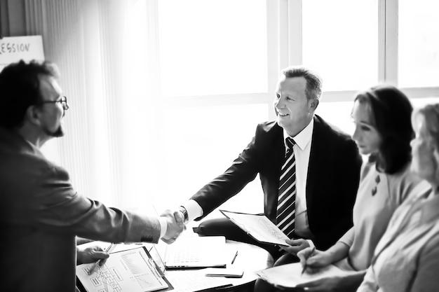 Handshake of senior business partners on the desk in the office