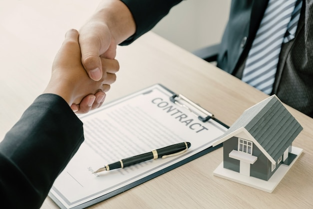 Рукопожатие: агент по недвижимости объясняет деловой контракт покупательнице.