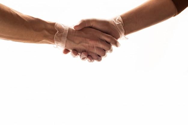 医療用手袋で握手。コロナウイルス防止。 covid 19