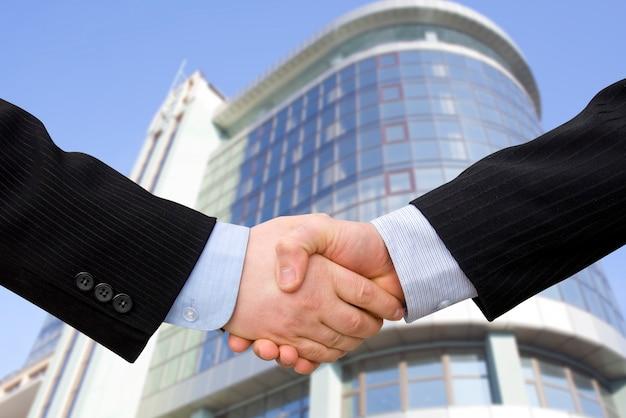 背景として現代の高層ビルと握手