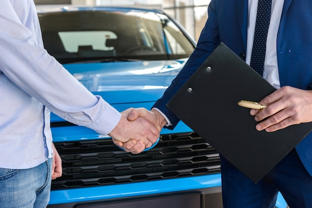 Handshakes about car buy deal close up
