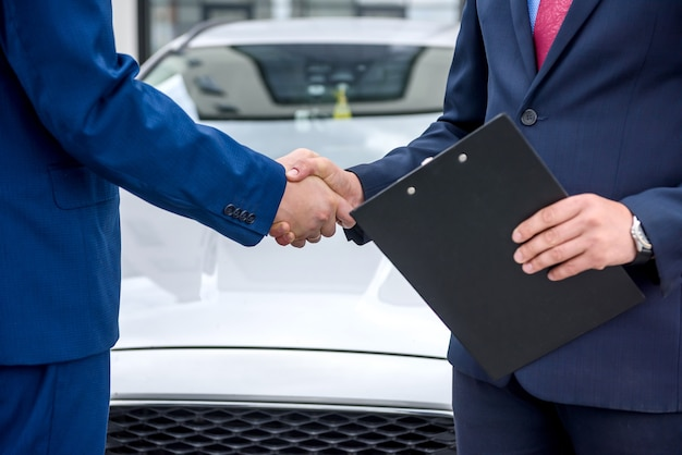 Handshakes of two men against hood of a car