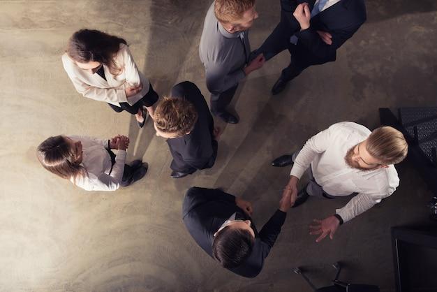 チームワークとパートナーシップの二重露光のオフィスコンセプトでハンドシェイクビジネスパーソン