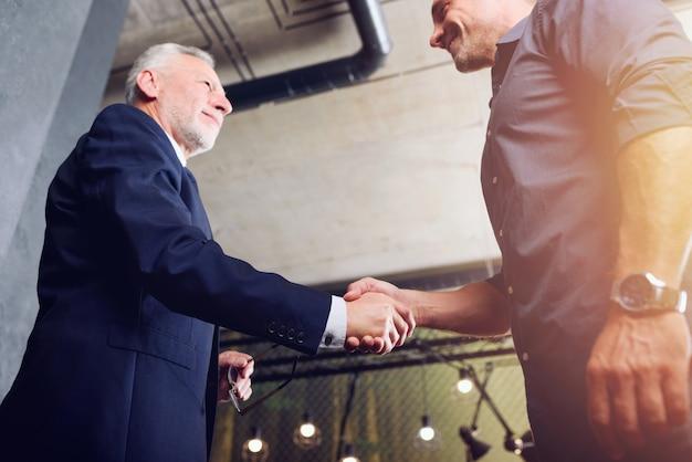 オフィスで握手するビジネスパーソン。チームワークとパートナーシップの概念。