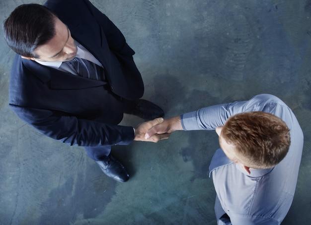 オフィスで握手するビジネスパーソン。チームワークとビジネスパートナーシップの概念