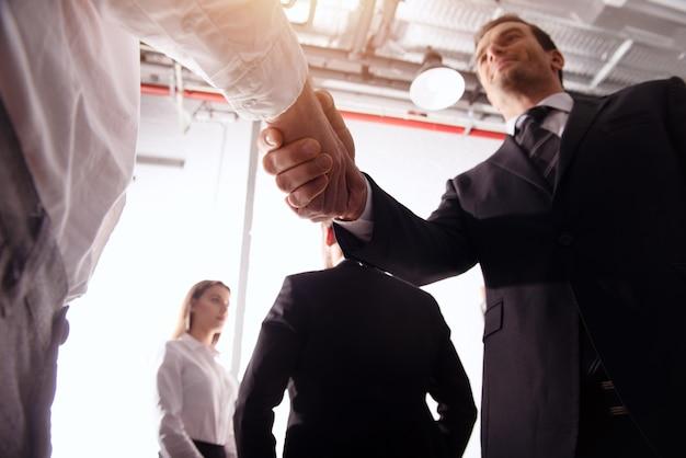 オフィスで握手するビジネスパーソン。チームワークとビジネスパートナーシップの概念。