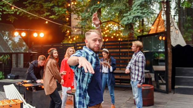 Handsome 30s caucasian young man dancing on near the camera on the background of his friends at the party in cozy evening garden.