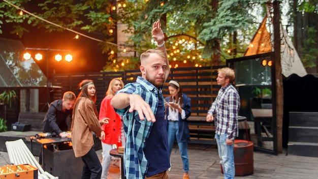 居心地の良い夜の庭でのパーティーで彼の友人の背景にカメラの近くで踊るハンサムな30代白人の若い男。
