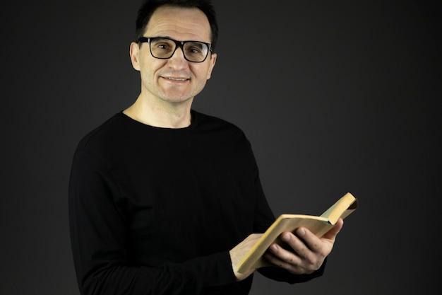 メガネで黒髪のハンサムな40代男性が手で本を持っています