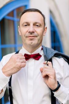 赤い蝶ネクタイを調整し、カメラに微笑んでフォーマルな服装でハンサムな50歳の男性