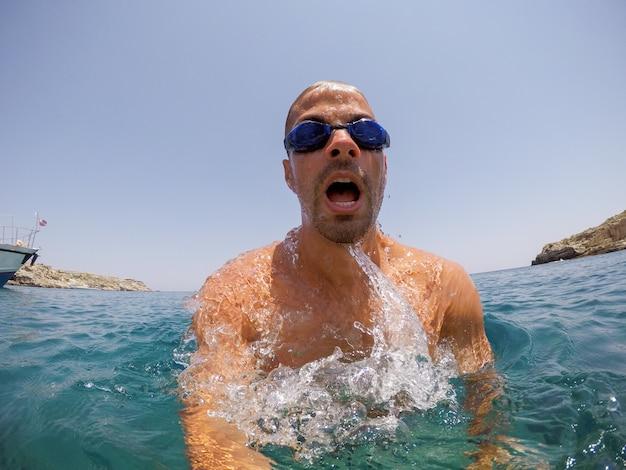 夏のエキゾチックな海で楽しんでいるハンサムなアクティブダイバー若い男。