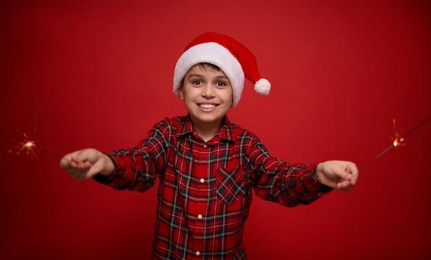 Красивый очаровательный малолетний мальчик, красивый ребенок в шляпе санта-клауса и клетчатой рубашке наслаждается рождественской вечеринкой, играет с бенгальскими огнями, бенгальскими огнями, изолированным или красным фоном с копией пространства для рекламы