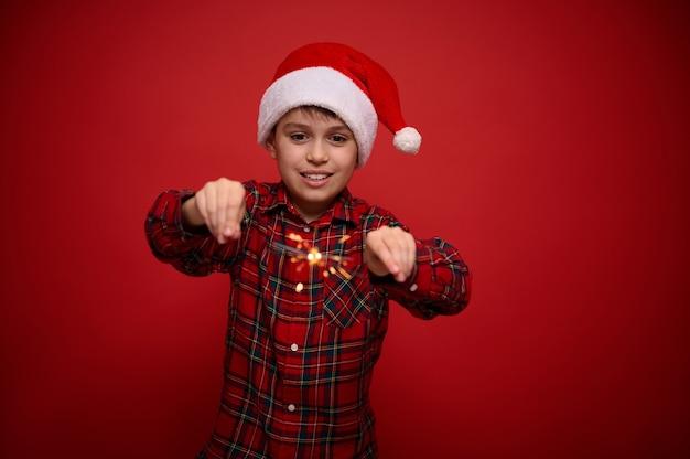 Красивый очаровательный малолетний мальчик, симпатичный ребенок в шляпе санта-клауса и клетчатой рубашке наслаждается рождественской вечеринкой, играет с бенгальскими огнями, бенгальскими огнями, изолированными на красном фоне с копией пространства для рекламы