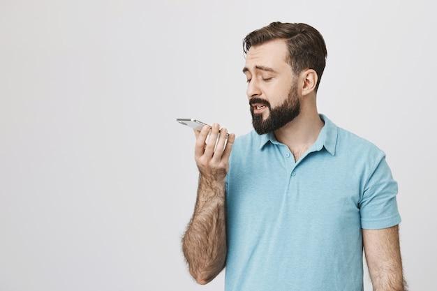 ハンサムな大人のひげを生やした男が電話でスピーカーでボイスメッセージを録音