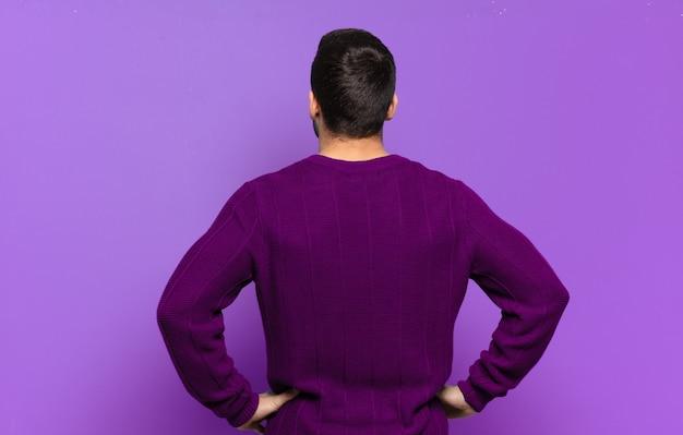 잘생긴 성인 금발 남자는 혼란스럽거나 가득 차거나 의심과 질문을 느끼고 엉덩이에 손을 얹고 후면 보기