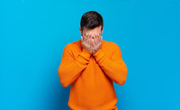 슬프고, 좌절하고, 긴장하고, 우울하고, 양손으로 얼굴을 덮고, 울고있는 잘 생긴 성인 금발 남자