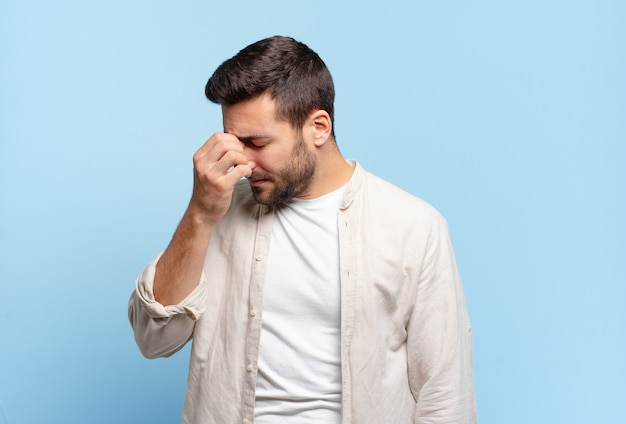 ストレス、不幸、欲求不満を感じ、額に触れ、激しい頭痛の片頭痛に苦しんでいるハンサムな大人のブロンドの男