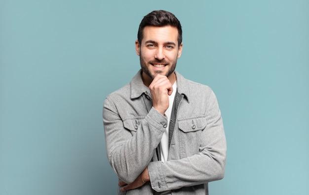 잘 생긴 성인 금발 남자가 행복하고 턱에 손으로 웃고 궁금해하거나 질문하고 옵션을 비교합니다.