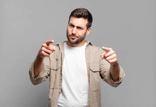 손가락과 화난 표정으로 카메라를 앞으로 가리키는 잘 생긴 성인 금발 남자, 당신의 의무를 다하라고 말합니다.