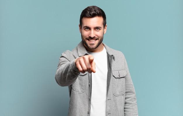 満足のいく、自信を持って、フレンドリーな笑顔で指さすハンサムな大人のブロンドの男、あなたを選ぶ
