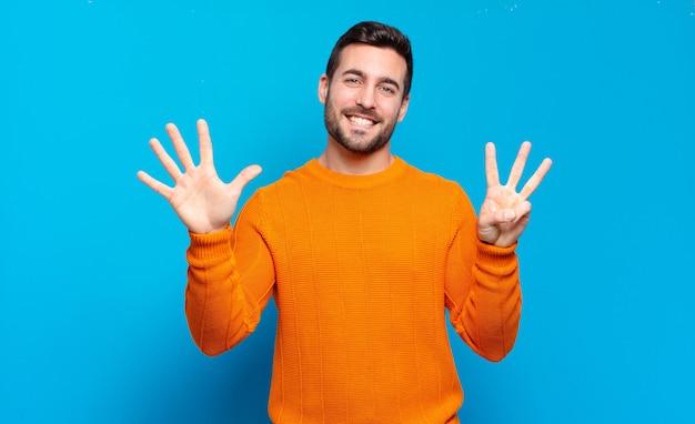 笑顔でフレンドリーに見えるハンサムな大人のブロンドの男、前に手を前に、カウントダウンで8番または8番を示しています