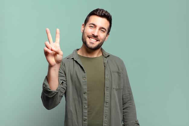Красивый взрослый белокурый мужчина улыбается и выглядит счастливым, беззаботным и позитивным, жестикулируя победу или мир одной рукой