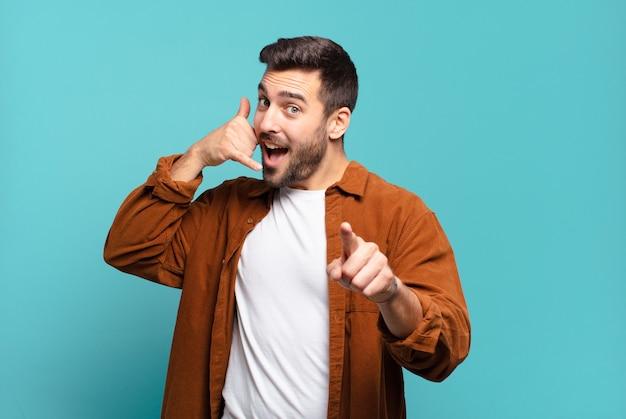 ハンサムな大人の金髪の男が明るく微笑み、後であなたに電話をかけながら指さし、電話で話しているジェスチャー