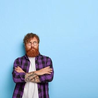 Красивый взрослый парень с рыжими волосами и бородой, скрестив руки на груди, недовольно смотрит