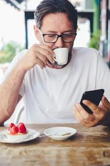 コーヒーを飲み、携帯電話でメールやニトフィケーションをチェックしているハンサムな成人男性。インターネット無線接続を楽しんでいるカフェで現代の成熟した人々