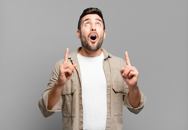 Handsome adult  man looking shocked, amazed and open mouthed, pointing upwards with both hands to copy space