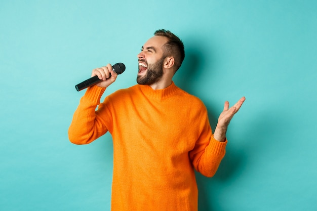 Handsome adult man perform song, singing into microphone, standing against turquoise wall