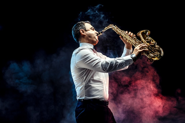 Handsome adult man playing saxophone