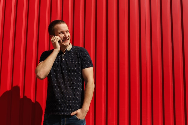 Handsome adult man using his cellphone, talking on red background with free space. happy young man standing over red wall background with mobile phone