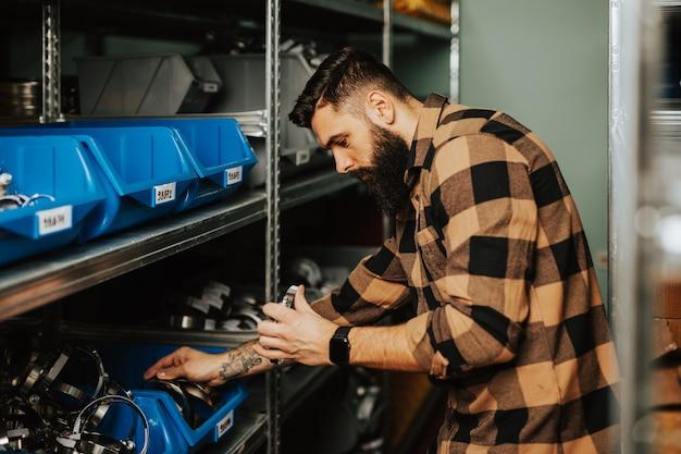 Красивый взрослый человек, работающий на складе запасных частей для автомобилей и грузовиков.