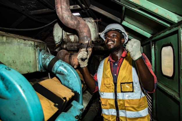 ハンサムなアフリカ系アメリカ人のインダストリアル エンジニアリングは、駅のガレージ プラントのエンジンについて、ウォーキー タキエで計画と議論をしている