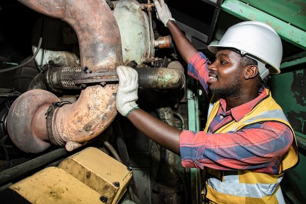 ハンサムなアフリカ系アメリカ人の産業工学計画と、ヘルメットと手袋をはめた駅のガレージ プラントのエンジンについて議論