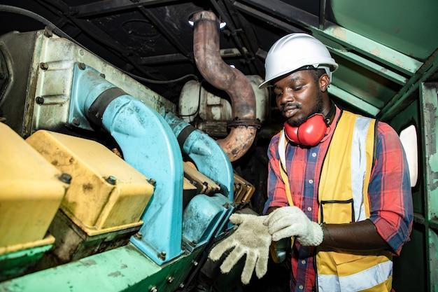ハンサムなアフリカ系アメリカ人のインダストリアル エンジニアリングは手袋をはめ、ヘルメットをかぶって駅のガレージ プラントのエンジンについて話し合う