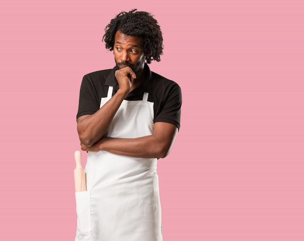 Handsome african american baker doubting and confused, thinking of an idea or worried about something